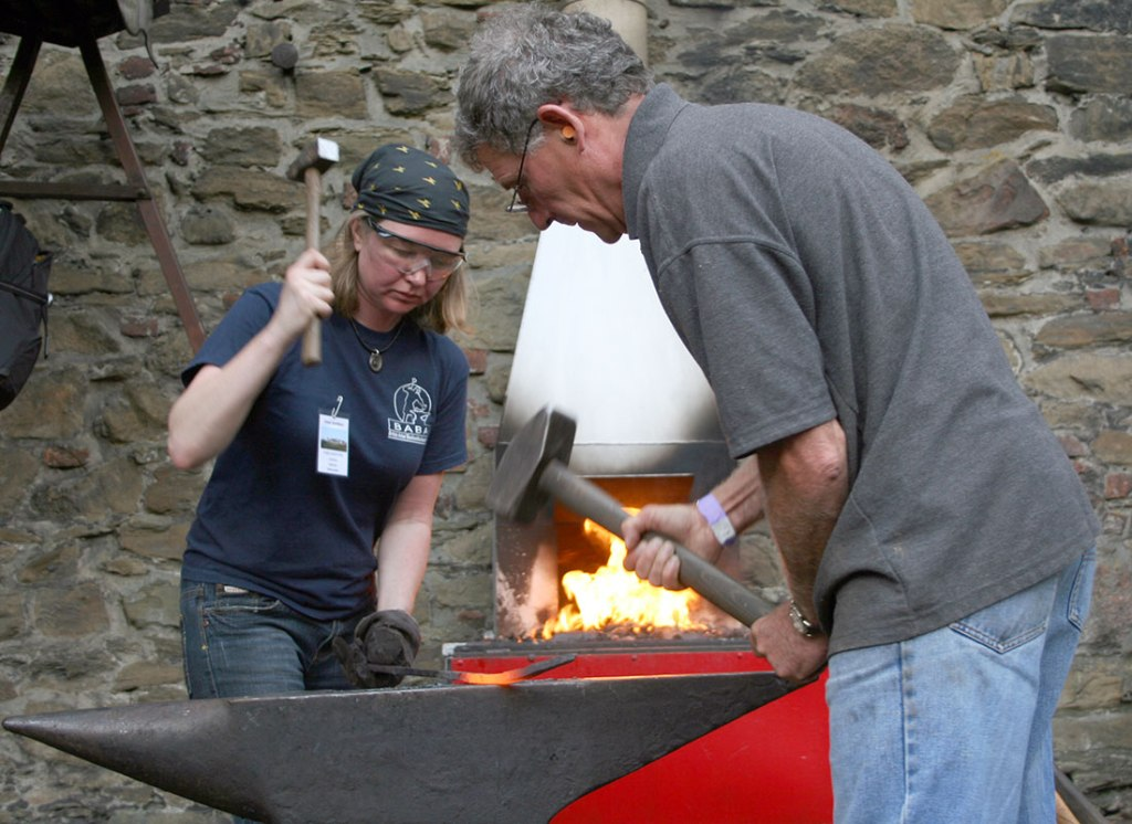 Chris Topp and Bethan Griffiths, blacksmiths, forging during a collaborative European blacksmithing project.